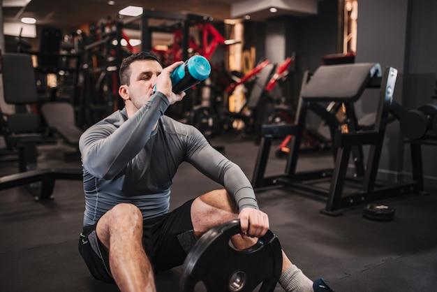 筋肉男は、ジムの床に座って水を飲む。