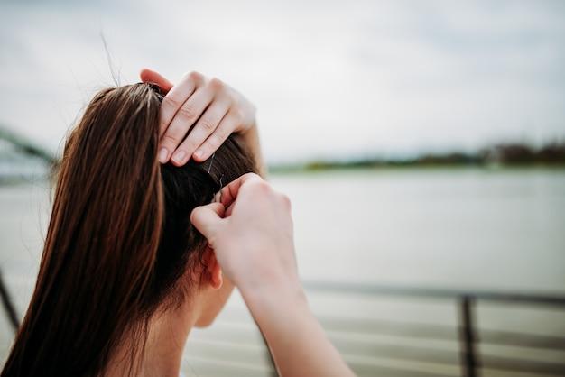屋外の髪にボビーピンを入れている女の子。閉じる。