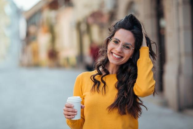カメラに微笑んで、街で行くコーヒーと美しいカジュアルなブルネット。