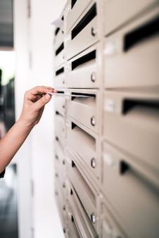 郵便受けに白い封筒を入れて手。