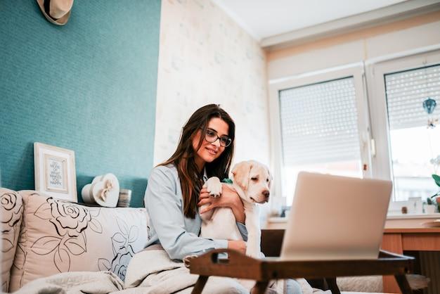 Девушка с щенком, имея видео звонок на ноутбуке.