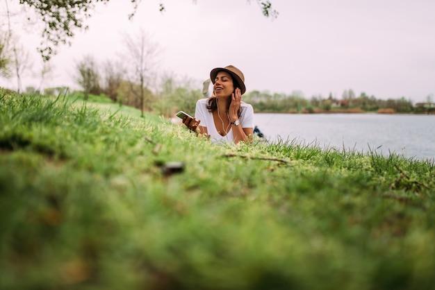 リラックスした女性は草の上に横になっているヘッドフォンで音楽を聴きます。