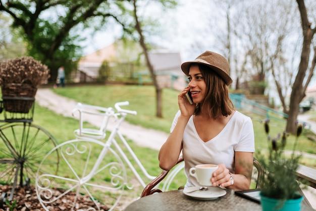 Усмехаясь женщина используя ее умный телефон пока сидящ на саде кафа.