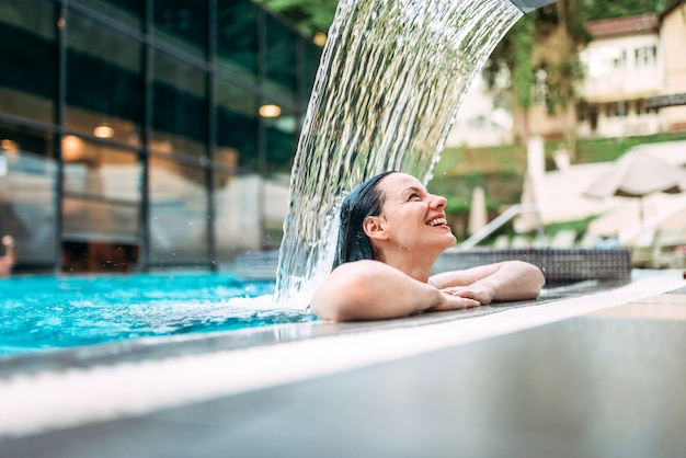 美しい若い女性は、スイミングプールの水の流れの下で温泉水のトリートメントでリラックスしました。