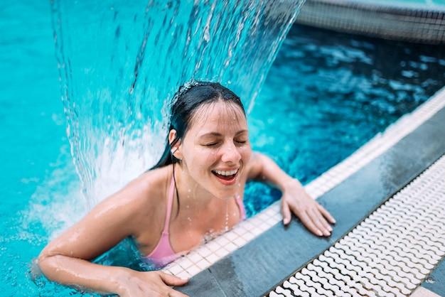 プール内の水の流れの下で笑顔の女性のクローズアップ。