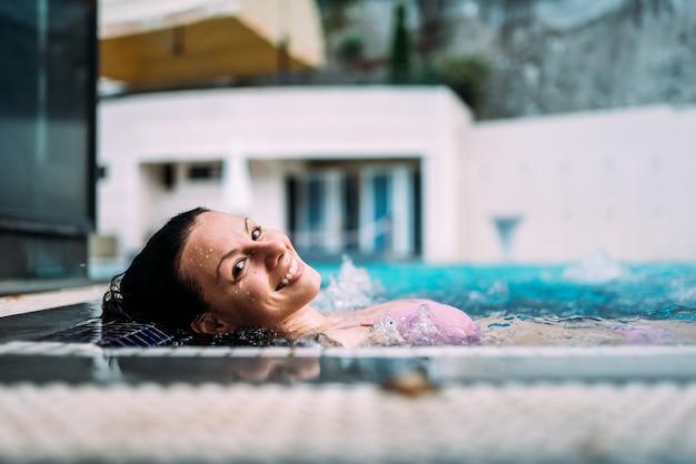 屋外ホットタブでリラックスした美しい女性のクローズアップ画像。