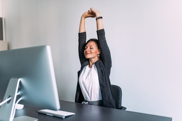 Перерыв на работе. женский офисный работник, протягивая руки.