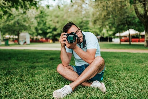 旅行、冒険、休暇の概念。カメラマンは公園の芝生の上に座っています。