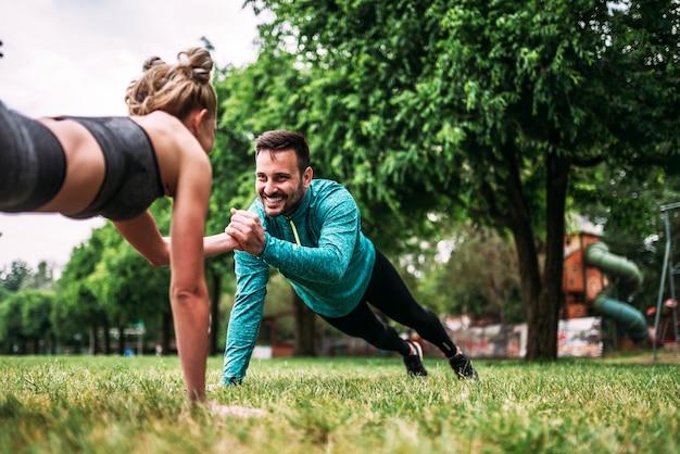 公園で片手押し上げ運動をしている若いカップル。
