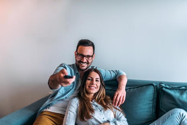 家でテレビを見ているカップル。正面図。