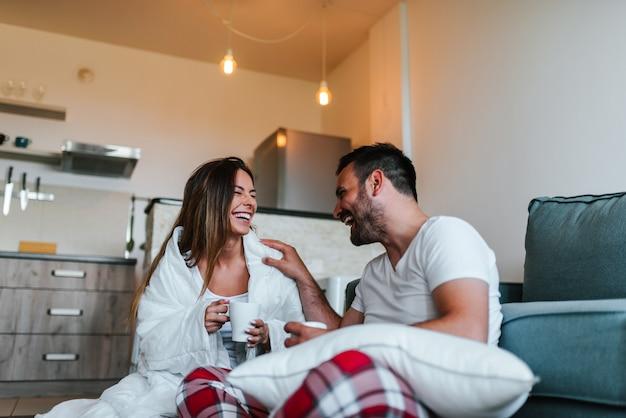 自宅でパジャマを着ている若いカップル。