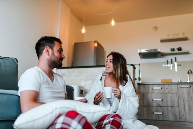 リビングルームの毛布の下のソファでくつろいでパジャマのカップル。朝はコーヒーや紅茶を飲みます。