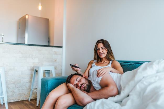 Молодая женщина смотрит телевизор, пока ее муж спит на коленях.