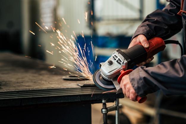 金属を研削する労働者のクローズアップイメージ。