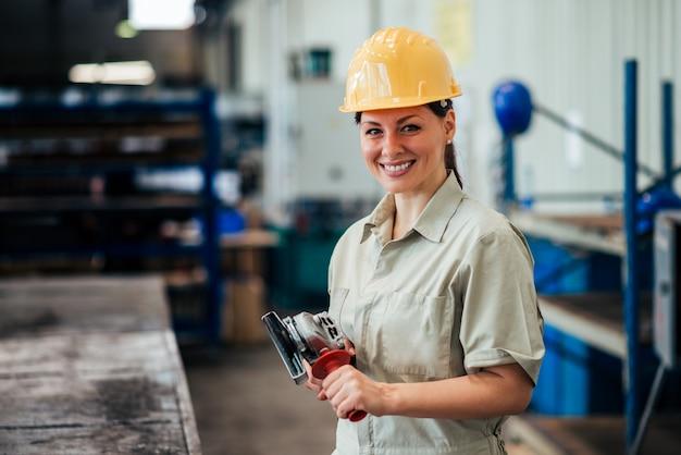 カメラで笑顔の仕事でグラインダーで女性の産業労働者の肖像画。