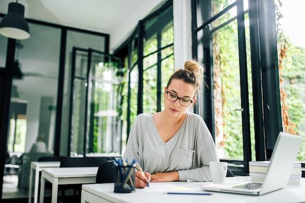 Изображение конца-вверх вскользь эссе сочинительства молодой женщины на столе.