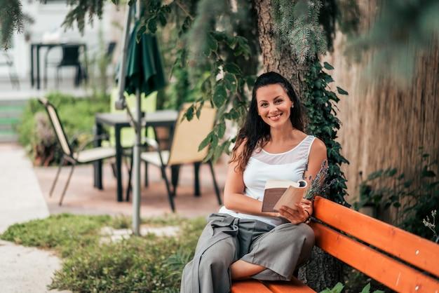 屋外の本を持つ美しい若い女性の肖像画。