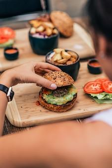 ベジタリアンバーガーを食べる若い女性。背面図