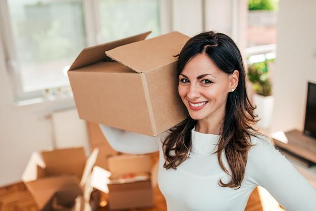 笑顔の若い女性が新しい家に移動のクローズアップ画像。