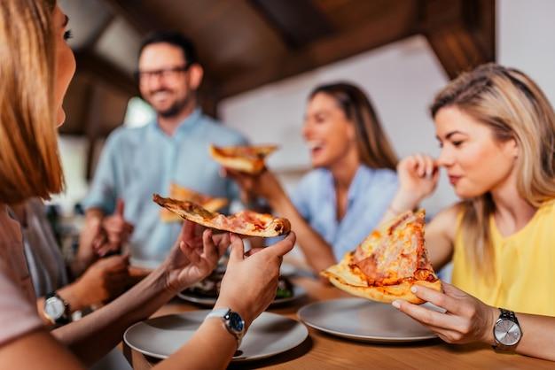 ピザを食べている友人や同僚のグループのクローズアップ画像。