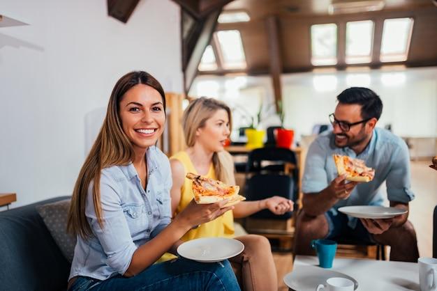 幸せな事業チームのオフィスでピザを食べます。