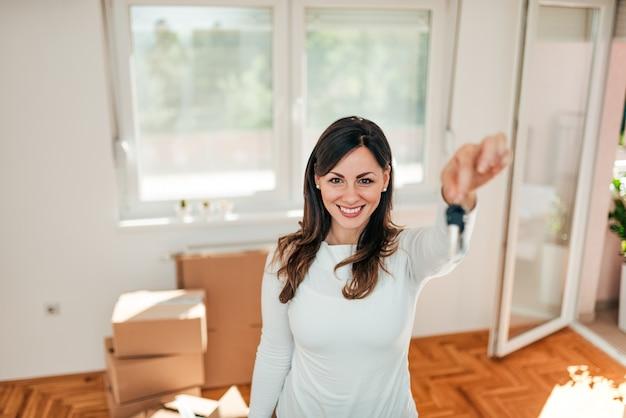 カメラへの鍵を示す笑顔の若い女性。新しい家に引っ越す。