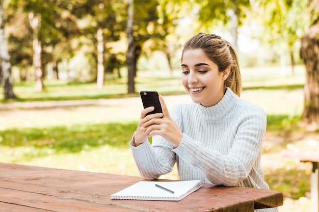 秋の公園でスマートフォンで入力する美しい女性の肖像画。