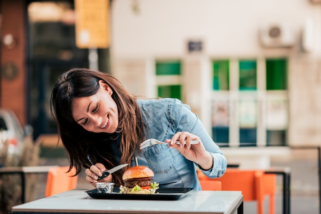 おいしいハンバーガーを楽しんでいる若い女性。