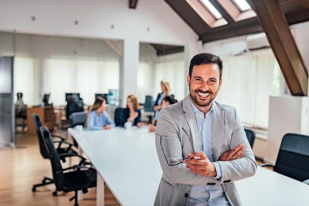 オフィスで笑っているハンサムなエグゼクティブ