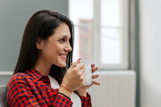 若い女性が休憩時間にコーヒーのマグカップを飲みます。