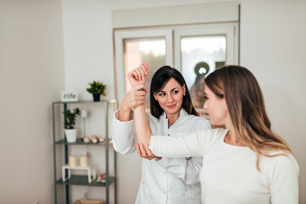 医者は診療所で患者の腕を調べます。
