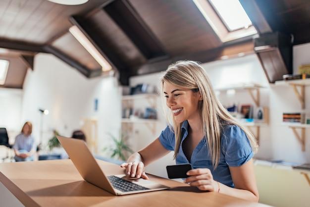 Счастливая молодая женщина делает электронные покупки.