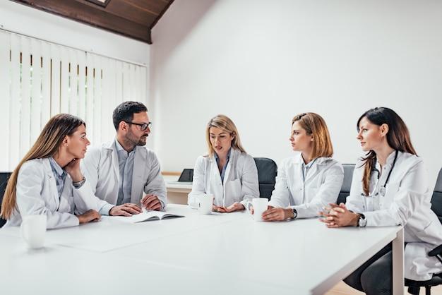 会議室に座って話している医師のチーム。スペースをコピーします。