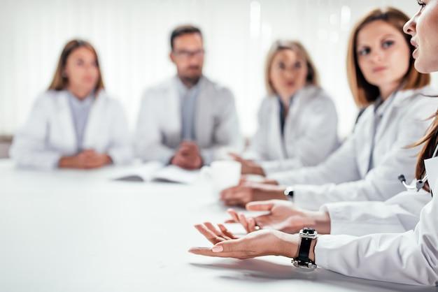 会議中に議論している医師の画像をトリミングしました。スペースをコピーします。
