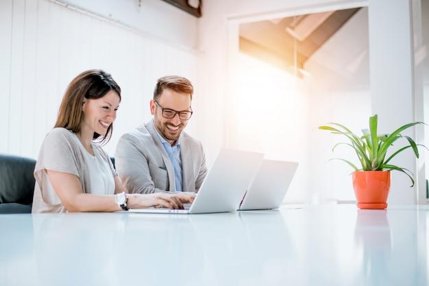 モダンなスタートアップのオフィスで一緒にプロジェクトに取り組んでいるビジネスカップル。