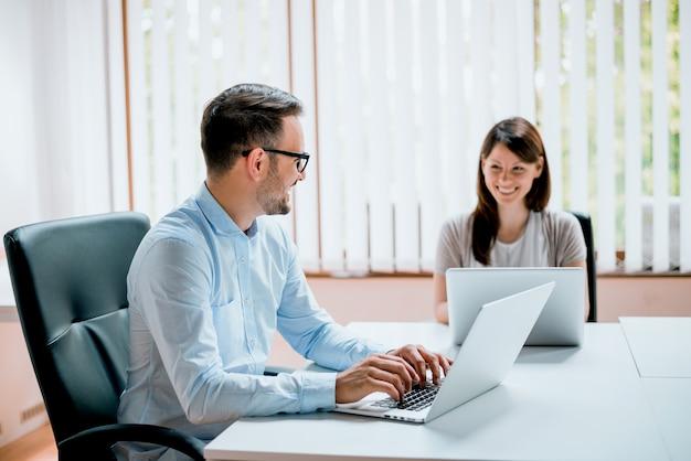 お互いを見てオフィスで働く若いビジネスマン。