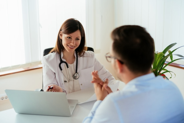 医者のオフィスで患者に話しています。