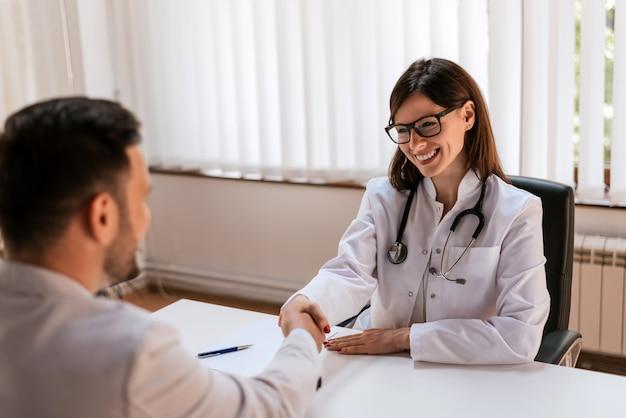 手を振って患者と診療所で幸せな女ブルネット医師。