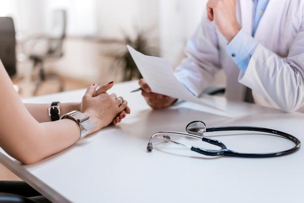 医者は医療診断のために患者と話しています。