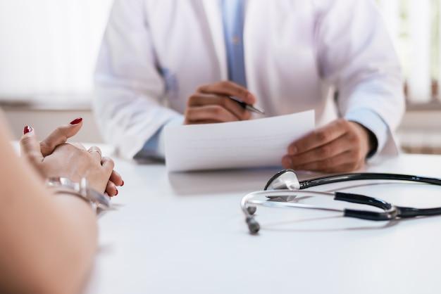 医師と患者が診断について話し合っています。医師が医療形態を見て、メモを取ります。
