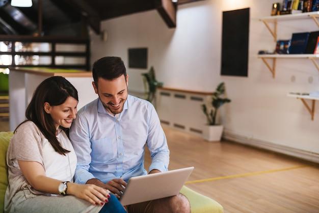 陽気なカップルが自宅のラップトップで何かを検索します。