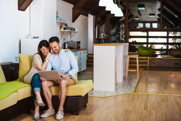 インターネットをサーフィンするラップトップコンピューターを備えた大きな快適なソファで一緒にリラックスした若いカップル。