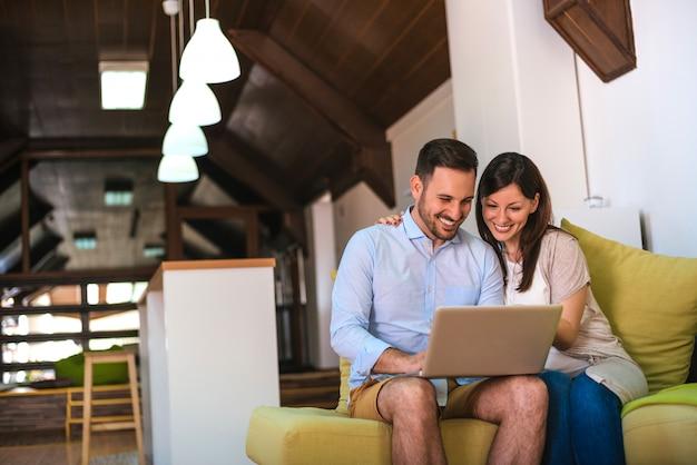 ソファに座りながらノートパソコンを使用して若いカップル