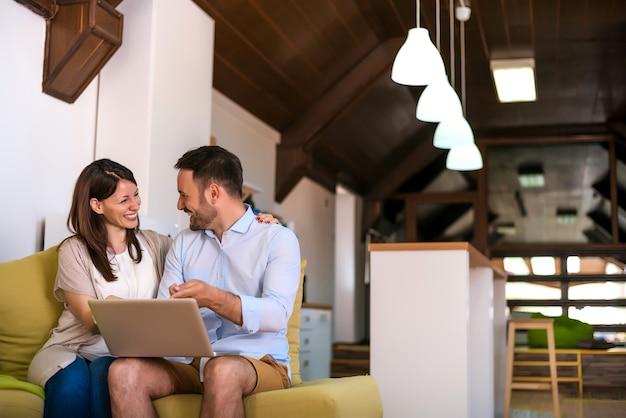 笑いカップルが自宅でインターネットを閲覧します。
