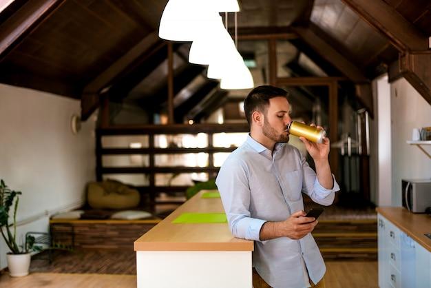 Человек с смартфон пьет пиво и текстовые сообщения