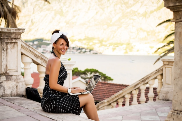 屋外のラップトップを使用してドレスの魅力的な若い女性