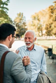 二人の男が公園でハンドシェイクします。先輩と若い男が公園で会います。家族の再会のコンセプトです。