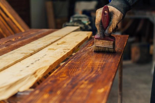 絵筆を使用して木の板をニス