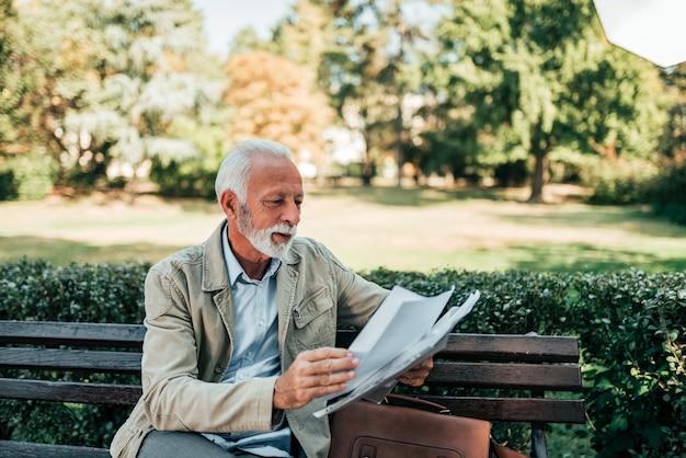Пенсионер читает газеты в парке.