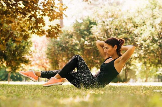 陽気な若い女性が公園で芝生に横になっている十字架クランチ運動をしています。